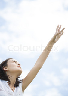 Young woman stretching her hand towards sky