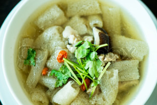 Braised Pork soup with Chinese herb and bamboo in white bowl
