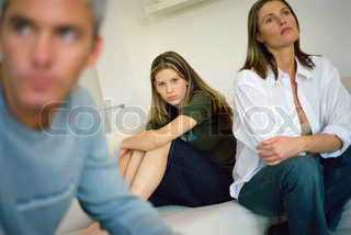 Girl sitting on bed hugging knees, parents sitting nearby looking away with air of frustration