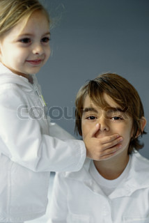 Sister covering brother's mouth with hand