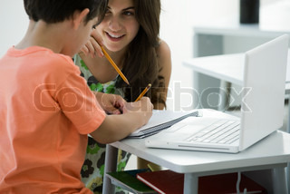 Girl teaching boy with laptop on table