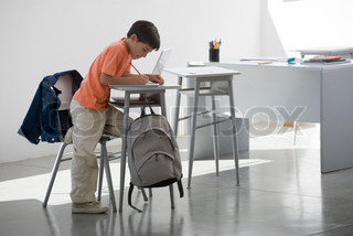 Student writing on table in the classroom