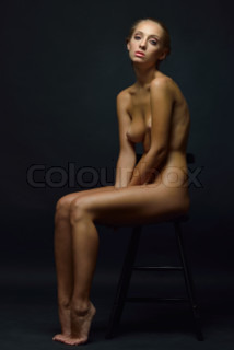 Beautiful tanned naked blonde woman sitting in studio.
