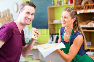 Saleswoman at counter offering cheese