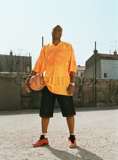 Man standing with a basketball in urban playground