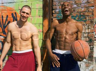 Laughing men holding basket ball and standing against graffiti wall