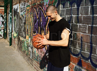 Man leaning on graffiti wall and holding basketball