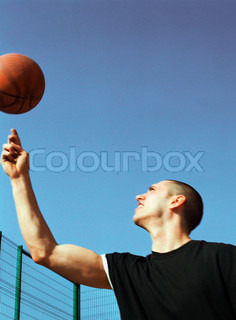 Man holding basketball and looking up
