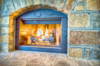 luxurious stone structure fireplace with burning fire