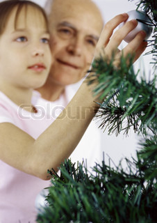 A grandfather and his grandchild decorating the Christmas tree