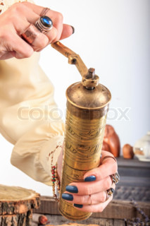 Woman holding old coffee grinder