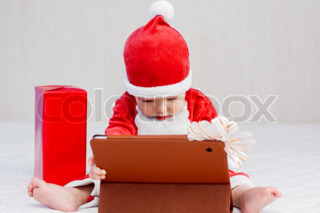 santa helper baby boy with digital tablet