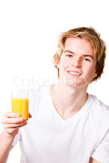 Portrait - young teenage caucasian boy holding a glass of orange juice