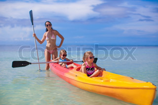 Young mother and two her little daughters kayaking at tropical warm sea