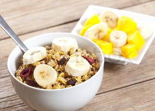 wunderbare gesunde Müsli mit Rosinen und frischen Mangos und Bananen.