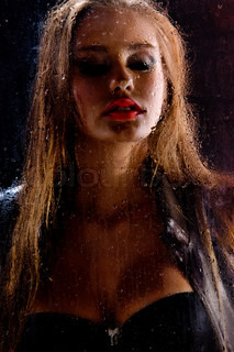 Sexy Beautiful Woman Behind Glass with Water Drops.