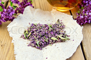 Oregano is dry on the paper with cup on board