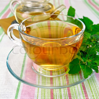 Tea with mint in cup and teapot on tablecloth