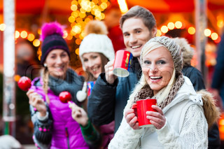 Friends with candy apple and eggnog on Christmas Market