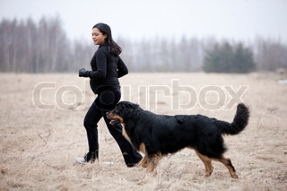 A pregnant woman and her pet dog running in the field