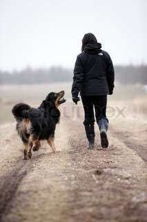 A pregnant woman and her pet dog  taking a walk in the field