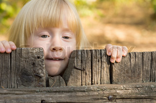 Pretty little blond girl peering over a fence