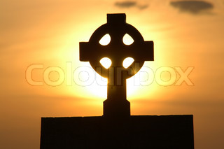 holy cross on a stone and sunset