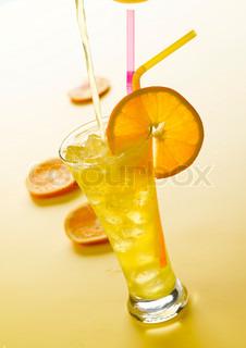 En festlig drink med appelsinskiver og sugerør som pynt