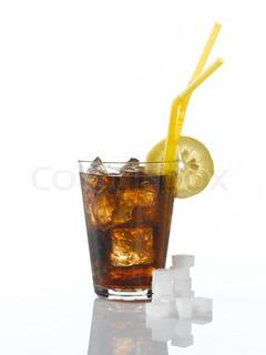 En kold cola med citronskive i kanten og sukkerknalder foran