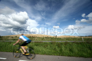 summer sky with nice cloud formation / cyclist passing by