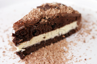 A chocolated cake ready for eating. Put on a white plate.
