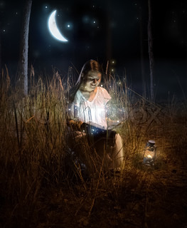 beautiful woman sitting at night forest and reading fairy tale book