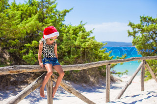 Cute little girl in christmas hat during beach vacation