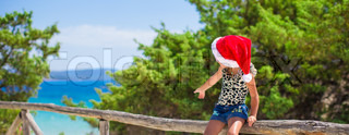 Adorable little girl in christmas hat during summer beach vacation