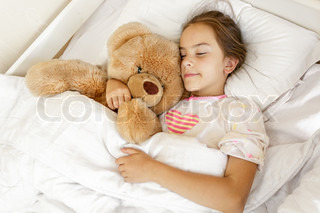cute girl sleeping and hugging big teddy bear at bed