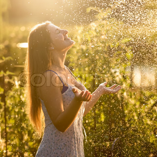 beautiful woman enjoying rain at sunny day at garden