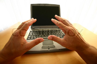 hand in front of a labtop