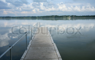 a lake in denmark with blue cloudy sky wood bridge