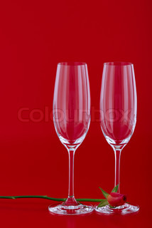 Two wine glasses with rose flower over red