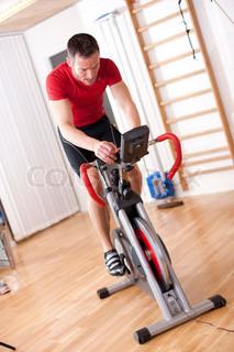Mand der cykler på en kondicykel