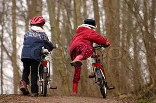 2 children with  bicycle in a forest