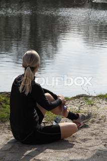 Blond sports kvinde sidder ved søen