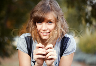 portrait of a beautiful young girl with brown hair on the background of nature