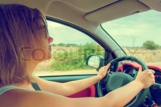 Woman in glasses driving car. Vintage effect photo.