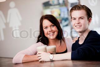 Et smilende kæresterpar der drikker kaffe sammen