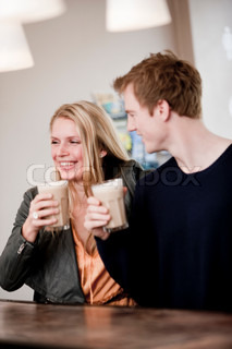 A young happy caucasian couple drinking cafe latte in a cafe/restaurant