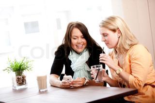 To unge piger der kigger på mobil sammen