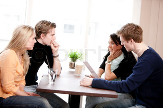 Two young caucasian couples on a double date in a restaurant/cafe