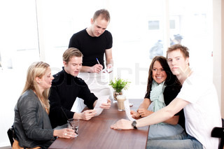 Two young caucasian couples ordering food from a waiter in a restaurant