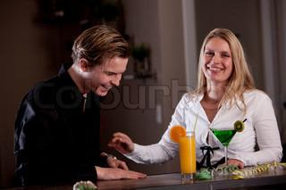 Et glad par der drikker inde på en bar
